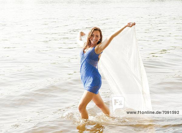 Junge Frau mit transparentem Tuch auf dem See