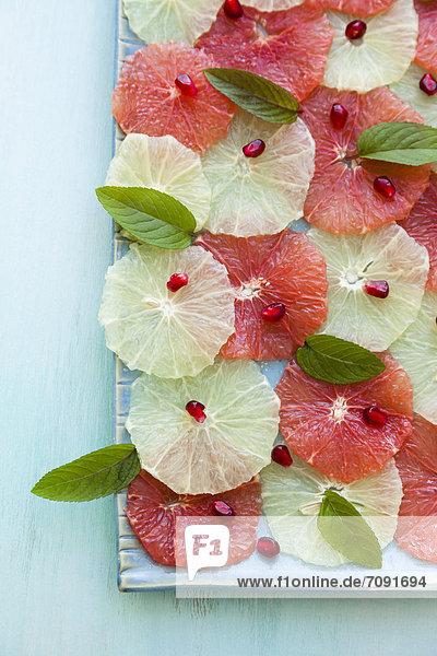 Orangen- und Rosa-Grapefruitsalat  garniert mit Granatapfelkernen und Minze auf dem Tablett Orangen- und Rosa-Grapefruitsalat, garniert mit Granatapfelkernen und Minze auf dem Tablett