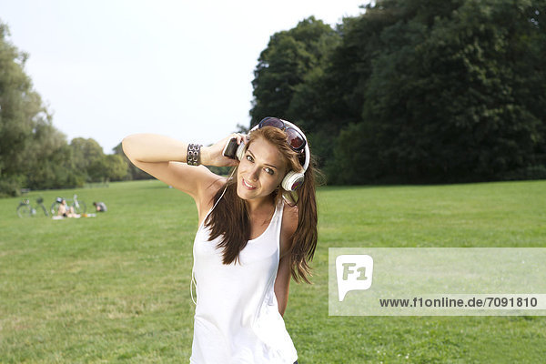 Young woman listening music at Treptower Park