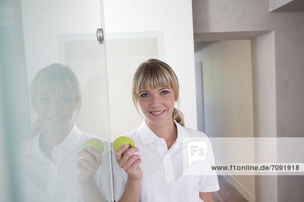 Germany  Dentist holding green apple  smiling  portrait