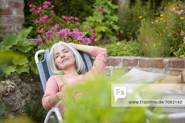 Mature woman relaxing in garden