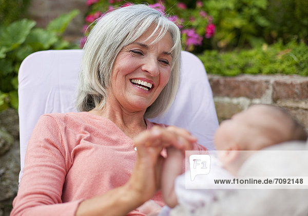 Woman with grandchild sitting in lawn chair  smiling
