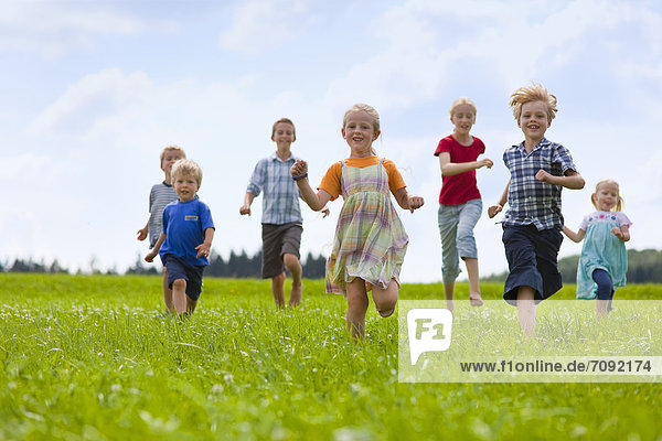 Germany  Bavaria  Group of children running through meadow