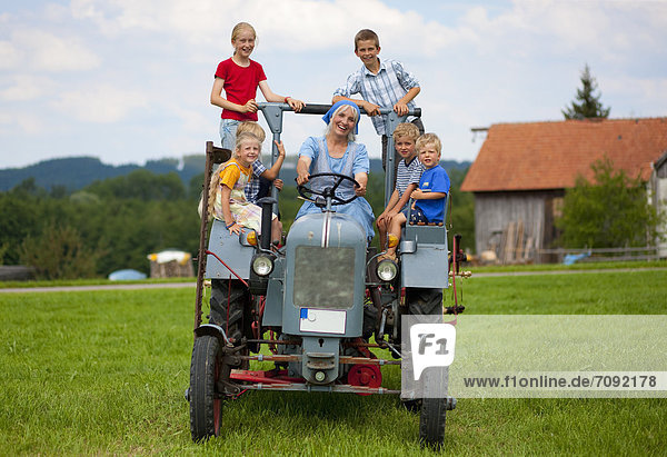 Woman with group of children sitting on old tractor in front of farmhouse