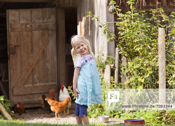 Girl with chicken on farm
