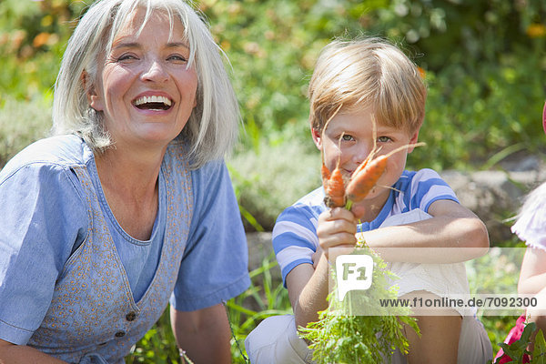 Mature woman and boy inspecting carrots in garden