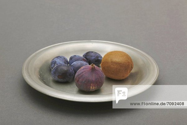 Plate of fruits on gray background