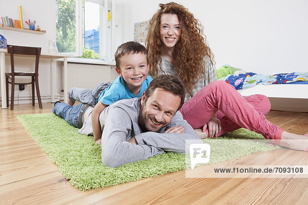 Germany  Berlin  Family lying on floor  smiling  portrait