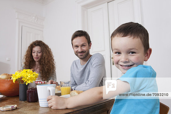 Germany  Berlin  Family having breakfast  smiling  portrait