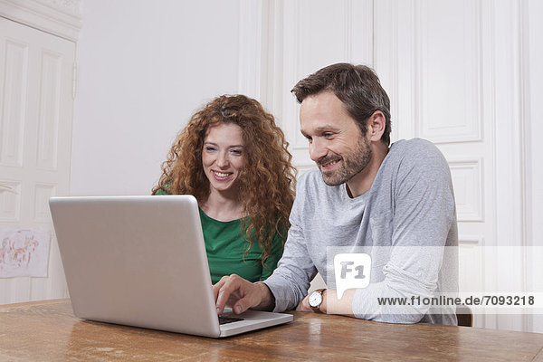 Germany  Berlin  Couple using laptop at home
