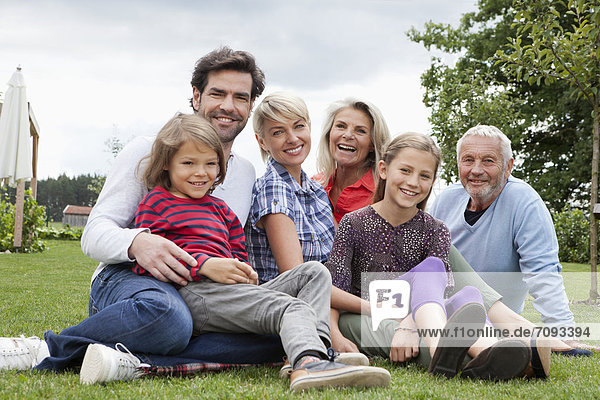 Germany  Bavaria  Nuremberg  Family sitting in grass  smiling  portrait