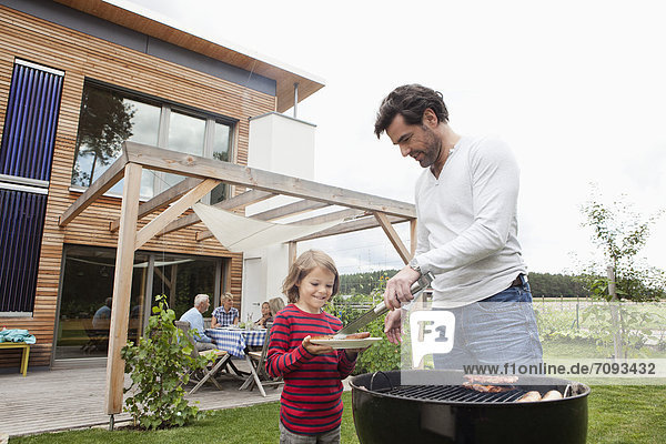 Germany  Bavaria  Nuremberg  Father and son preparing food on barbecue  family sitting in background