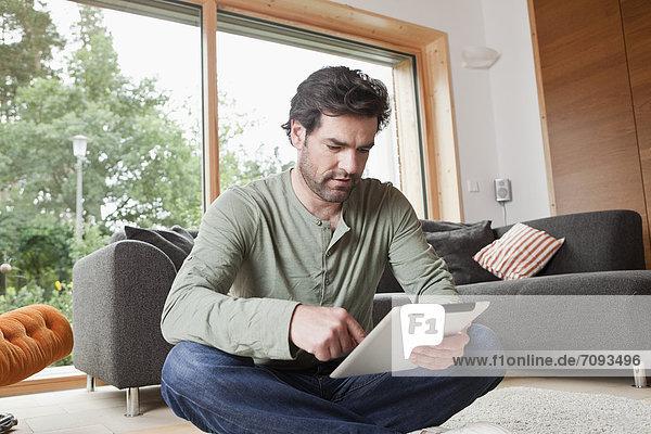 Erwachsener Mann mit digitalem Tablett im Wohnzimmer