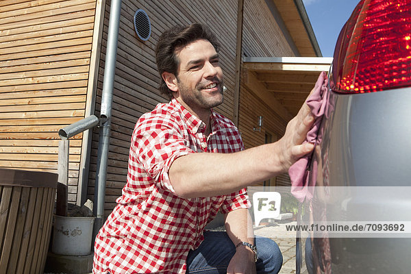 Mature man cleaning car in front of house