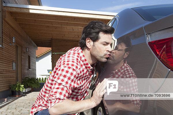 Erwachsener Mann küssendes Auto