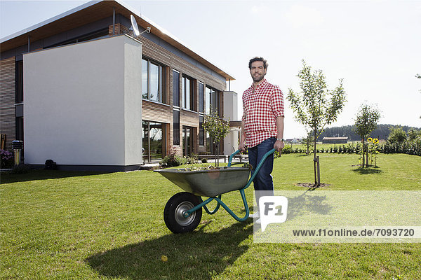 Erwachsener Mann mit Schubkarre im Garten