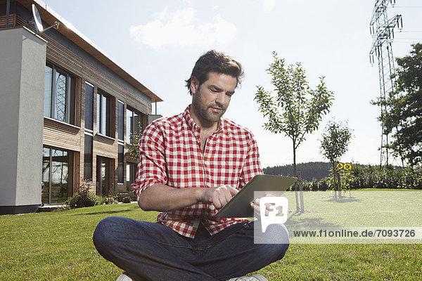 Erwachsener Mann mit digitalem Tablett im Garten