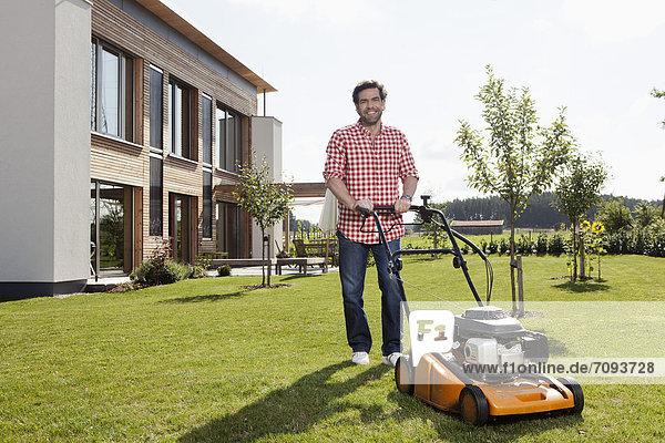 Erwachsener Mann mit Rasenmäher im Garten