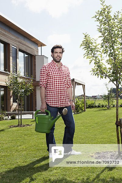 Mature man with watering can in garden