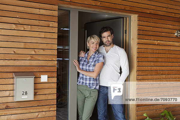Germany  Bavaria  Nuremberg  Mature couple standing at front door of house