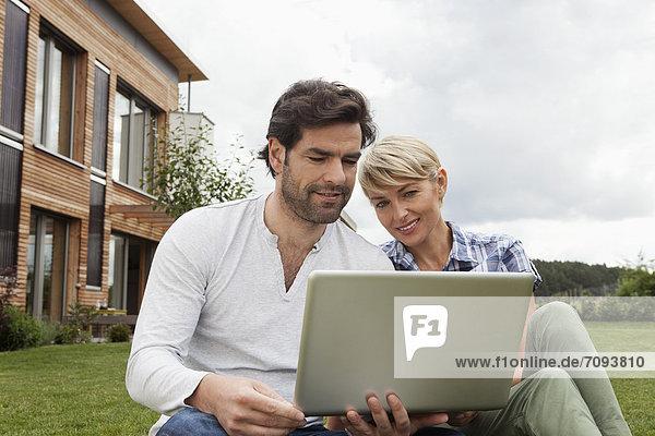 Germany  Bavaria  Nuremberg  Mature couple using laptop in garden