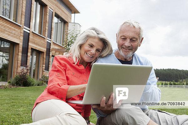 Deutschland  Bayern  Nürnberg  Seniorenpaar mit Laptop im Garten