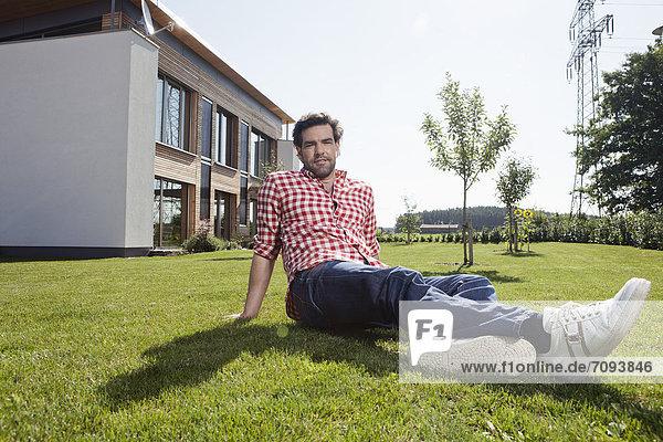 Erwachsener Mann im Garten sitzend