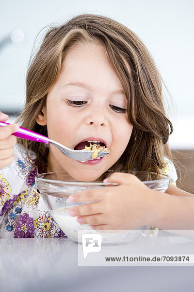Germany  Girl eating muesli in kitchen