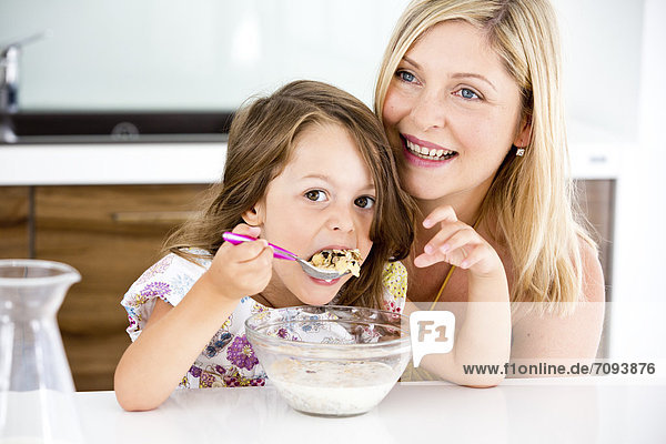 Germany,  Daughter eating muesli in kitchen