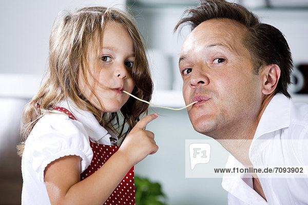 Germany  Daughter eating noodles with father in kitchen