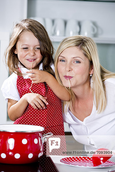 Germany  Mother and daughter eating noodles in kitchen