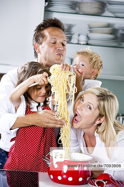 Germany  Family playing with spaghetti on kitchen worktop