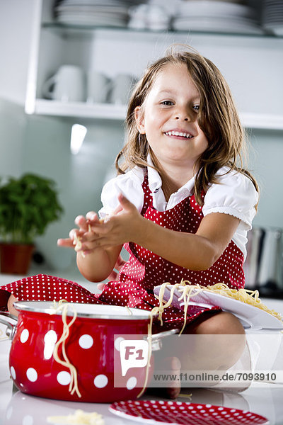 Germany  Girl playing with spaghetti  smiling  portrait