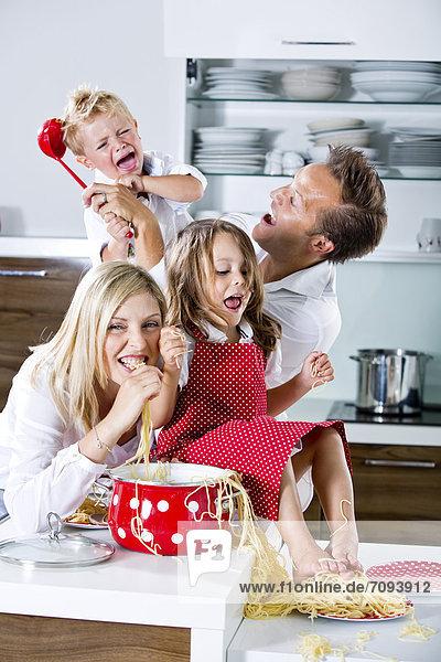 Deutschland  Familienspiel mit Spaghetti auf Küchenarbeitsplatte