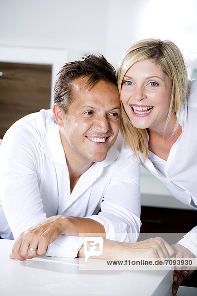 Germany,  Mid adult couple in kitchen,  smiling