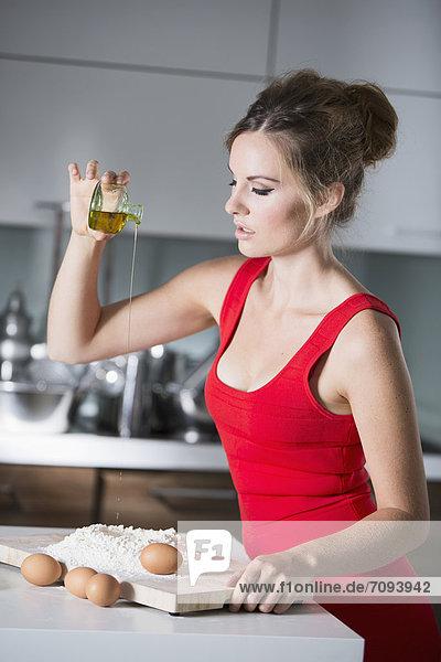 Deutschland  Junge Frau  die Öl in Mehl gießt