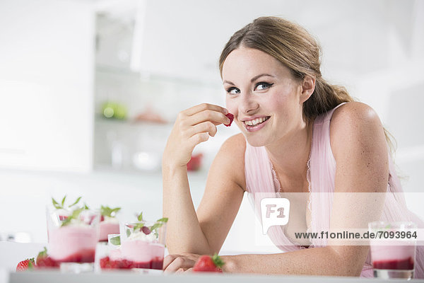 Germany  Young woman holding strawberry  smiling
