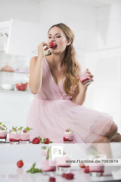 Deutschland  Junge Frau beißt Erdbeere  Gläser mit Erdbeerjoghurt