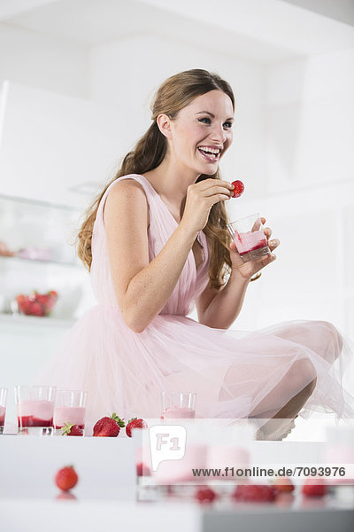 Germany  Young woman with glasses of strawberry yogurt  smiling