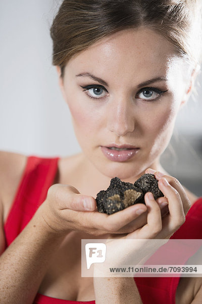 Germany  Young woman holding truffles  close up