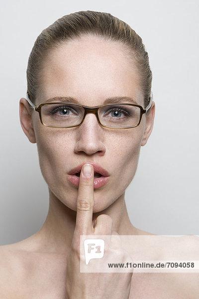 Junge Frau mit Finger auf den Lippen  Nahaufnahme  Mund