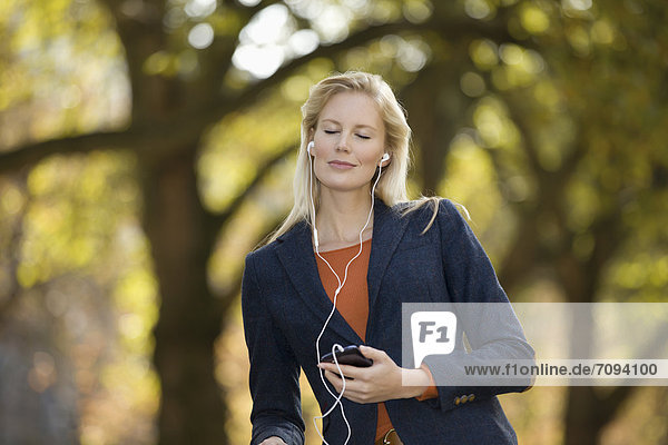 Europe  Germany  North Rhine Westphalia  Duesseldorf  Young woman listening music with smart phone  smiling