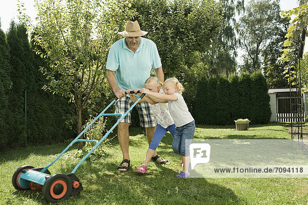 Germany  Bavaria  Grandfather with children mowing lawn