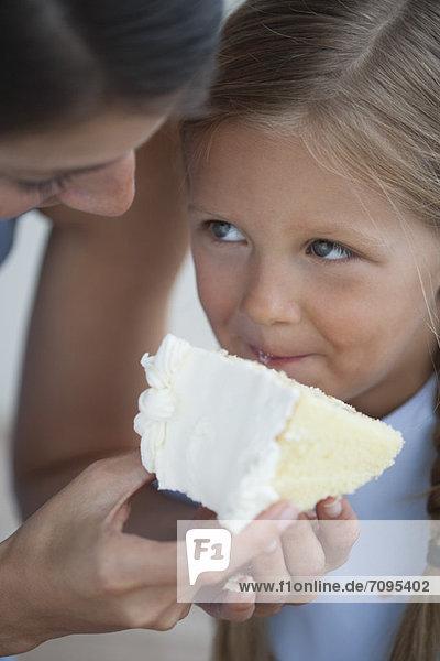 Mutter füttert ein Stück Kuchen an ein kleines Mädchen.