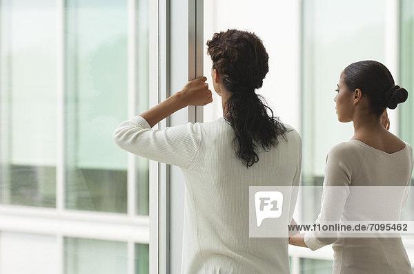Kollegen stehen nebeneinander und schauen aus dem Fenster  Rückansicht Kollegen stehen nebeneinander und schauen aus dem Fenster, Rückansicht