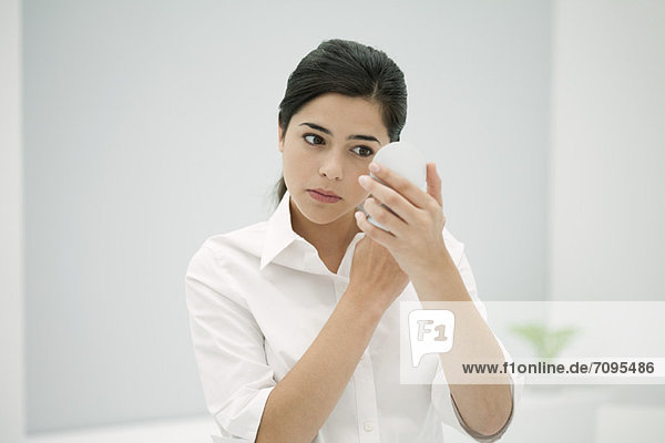 Young woman looking at self in hand mirror