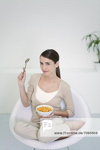 Junge Frau im Stuhl sitzend mit Getreideschale