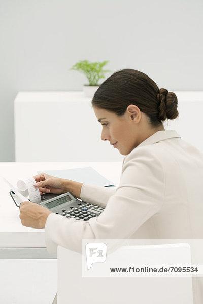 Frau  die den Ausdruck der Addiermaschine im Büro begutachtet