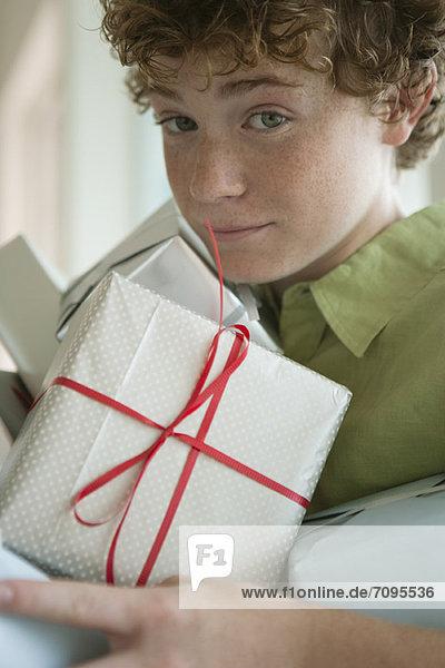 Ein Junge  der einen Haufen Geschenke hält.