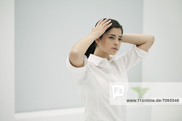 Young woman fixing hair  holding hairpin in mouth